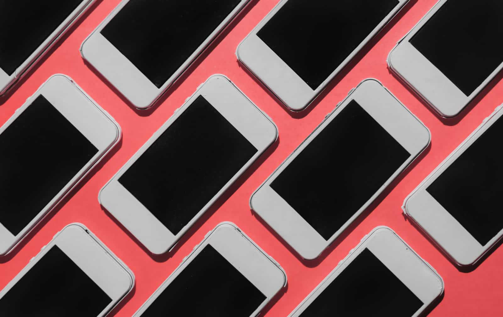 Mobile phones lined up on pink background