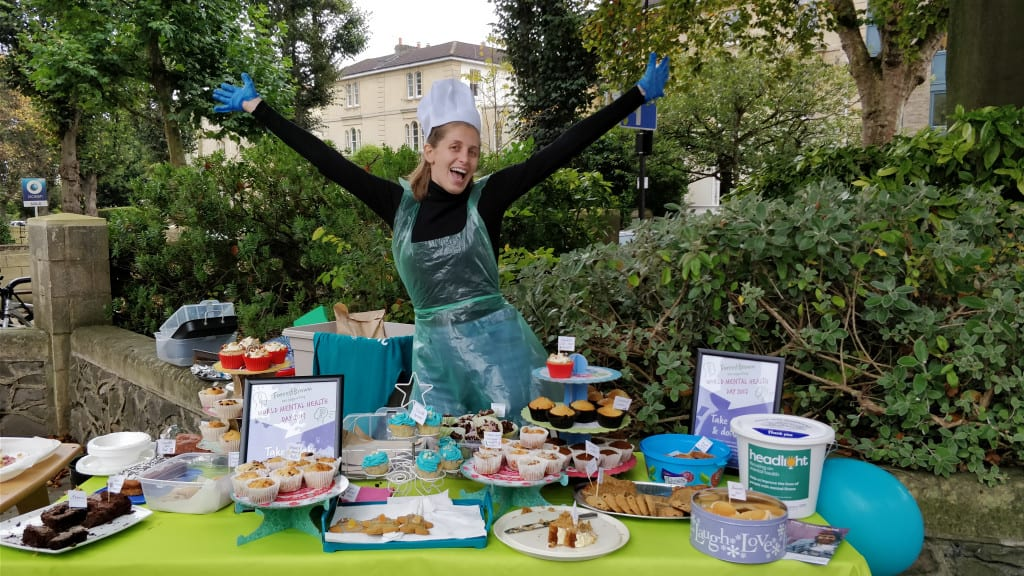 Ele and cakes at charity bake sale for Headlight Mental Health Charity