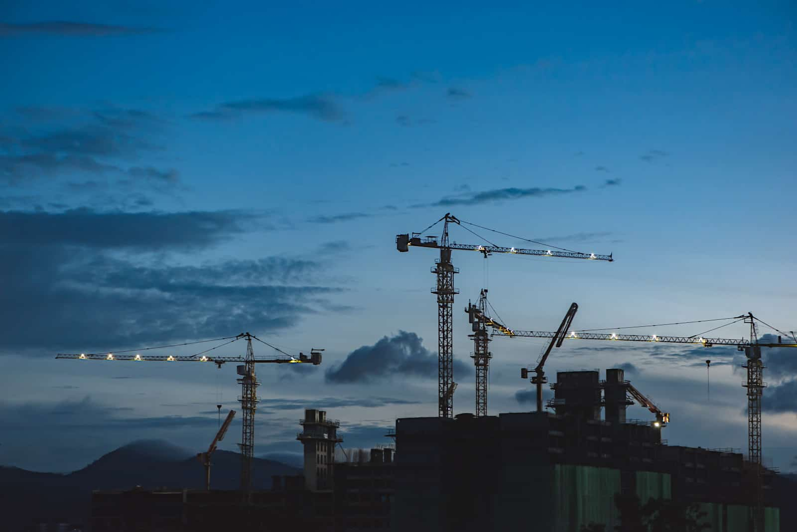 future of construction with cranes on skyline